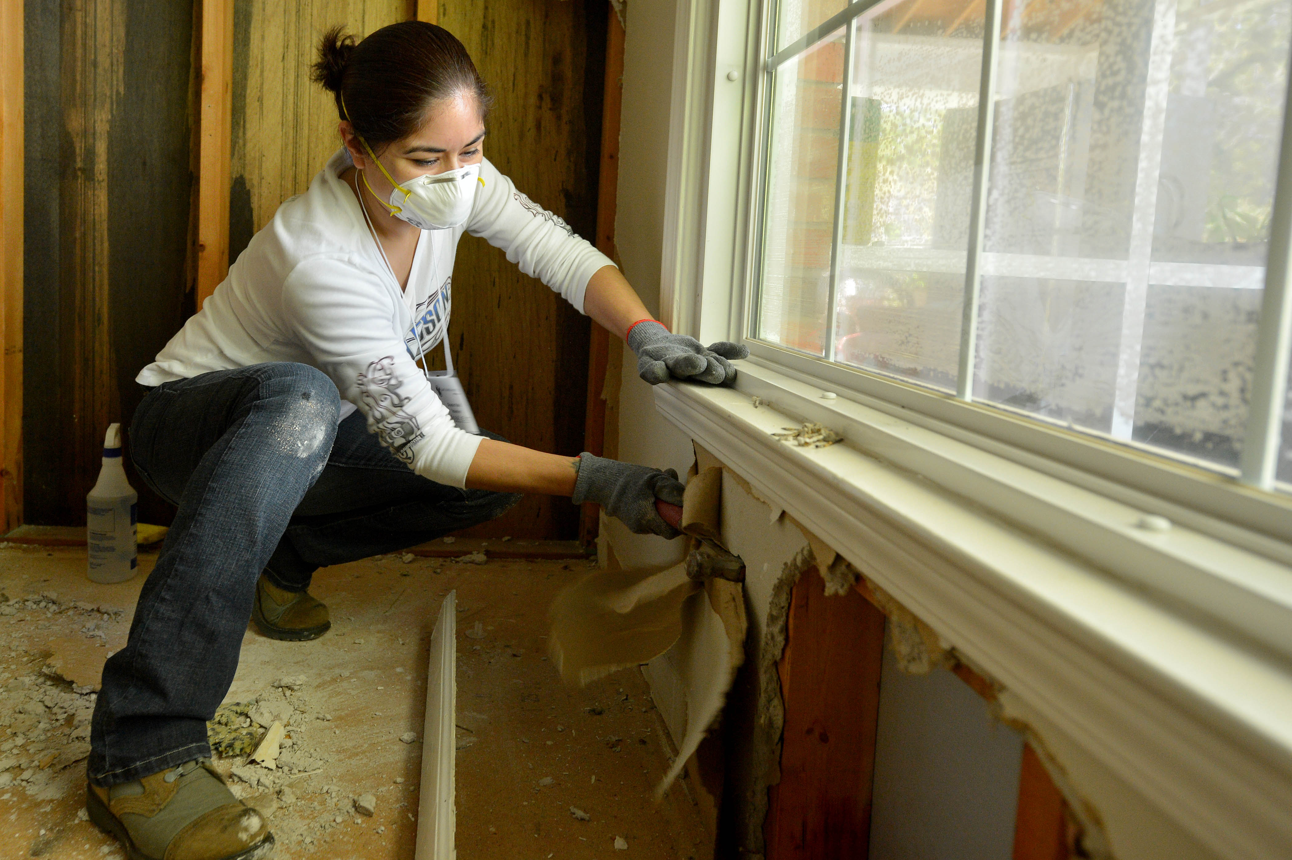 A woman helping to remove drywall from a flooded home.