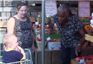 Mom and child talking with farmer at farmers market.
