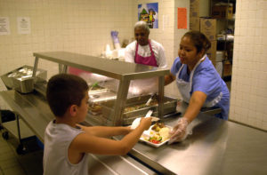 Cafeteria employee handling lunch to student